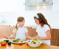 Hermanas hermosas del cocinero en la cocina que prepara la ensalada fotografía de archivo libre de regalías