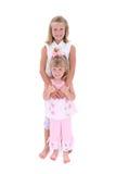 Hermanas hermosas en color de rosa sobre blanco Foto de archivo libre de regalías