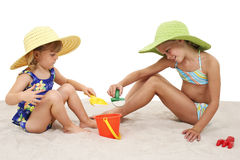 Hermanas hermosas en los sombreros de la playa que juegan en la arena Foto de archivo libre de regalías