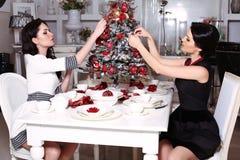 Hermanas hermosas que adornan el árbol de navidad en casa Fotos de archivo