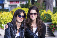 Hermanas hermosas que se sientan en un parque, la sonrisa y el abrazo Imagenes de archivo