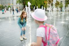 Hermanas jovenes lindas que juegan en fuentes en el cuadrado nuevamente renovado de Lukiskes en Vilna, Lituania Niños que se divi imágenes de archivo libres de regalías