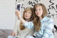 Hermanas lindas que ponen mala cara mientras que toma las fotos con el teléfono elegante en casa Fotografía de archivo