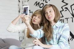 Hermanas lindas que ponen mala cara mientras que toma las fotos con el teléfono elegante en casa Imagenes de archivo
