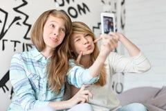 Hermanas lindas que ponen mala cara mientras que toma las fotos con el teléfono elegante en casa Fotografía de archivo libre de regalías