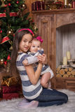 Hermanas lindas que se sientan en la alfombra blanca cerca del árbol de navidad y chimenea, suéteres rayados que llevan y vendas  imagenes de archivo