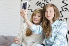 Hermanas lindas que toman las fotos con el teléfono elegante en casa Fotografía de archivo libre de regalías
