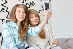 Hermanas lindas que toman las fotos con el teléfono elegante en casa Imagen de archivo libre de regalías