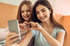 Hermanas magníficas que hacen un corazón mientras que toma el selfie Fotografía de archivo libre de regalías