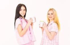 Hermanas o mejores amigos en pijamas Concepto del caf? de la ma?ana Rubio y moreno en caras sonrientes sostiene las tazas con caf imagen de archivo libre de regalías
