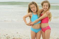 Hermanas que abrazan en la playa Fotografía de archivo libre de regalías