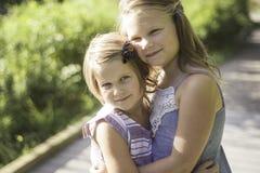 Hermanas que abrazan en un jardín en el tiempo de primavera Foto de archivo libre de regalías