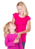 Hermanas que abrazan y que miran uno a Imagen de archivo libre de regalías