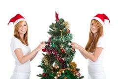 Hermanas que adornan el árbol de navidad Foto de archivo libre de regalías
