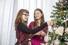Hermanas que adornan en el árbol de navidad en casa Foto de archivo