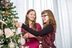 Hermanas que adornan en el árbol de navidad en casa Imagenes de archivo
