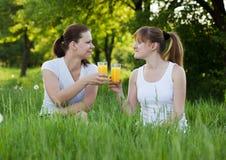Hermanas que beben el zumo de naranja en un parque Imágenes de archivo libres de regalías