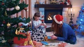 Hermanas que consideran sus regalos de la Navidad almacen de metraje de vídeo