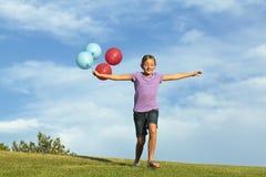 Hermanas que corren con los globos Imágenes de archivo libres de regalías