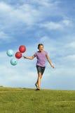 Hermanas que corren con los globos Imagen de archivo libre de regalías