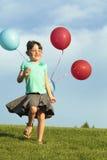 Hermanas que corren con los globos Fotografía de archivo libre de regalías