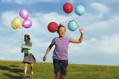 Hermanas que corren con los globos Foto de archivo libre de regalías