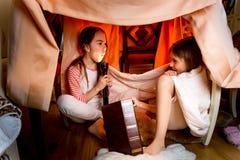 Hermanas que cuentan historias asustadizas debajo de la manta en la noche Fotografía de archivo libre de regalías