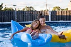 Hermanas que flotan en la piscina Fotos de archivo
