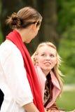 Hermanas que hablan en parque Imagen de archivo libre de regalías