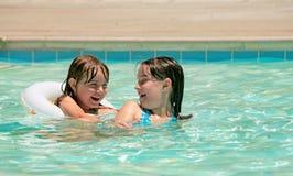 Hermanas que juegan en una piscina al aire libre Imágenes de archivo libres de regalías