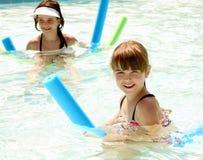 Hermanas que juegan feliz en una natación Foto de archivo