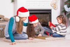 Hermanas que leen una historia de la Navidad Imagenes de archivo
