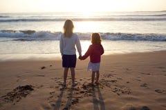 Hermanas que llevan a cabo las manos en la playa Fotografía de archivo libre de regalías