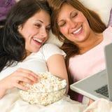 Hermanas que mienten en la cama que mira película divertida Foto de archivo