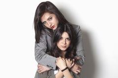 Hermanas que miran y que abrazan Foto de archivo libre de regalías