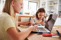 Hermanas que pasan tiempo así como los ordenadores en casa foto de archivo libre de regalías
