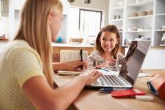 Hermanas que pasan tiempo así como los ordenadores en casa imagen de archivo