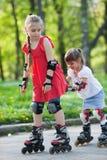 Hermanas que patinan en parque Imágenes de archivo libres de regalías