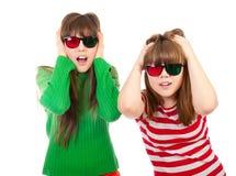 Hermanas que se divierten mientras que mira la película 3D Fotos de archivo libres de regalías
