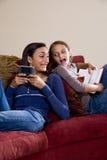 Hermanas que se relajan junto en el país en el sofá Fotografía de archivo libre de regalías