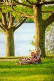 Hermanas que se sientan afuera Fotos de archivo libres de regalías