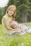 Hermanas que se sientan en el prado fotografía de archivo libre de regalías