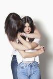 Hermanas que sonríen y que abrazan Imagen de archivo libre de regalías