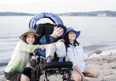 Hermanas que toman cuidado del hermano lisiado en la playa foto de archivo
