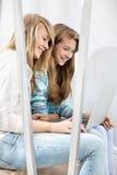 Hermanas que usan el ordenador portátil en la escalera Fotos de archivo libres de regalías