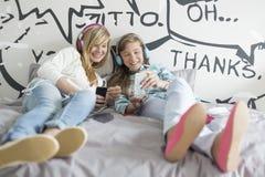 Hermanas relajadas que escuchan la música en casa Foto de archivo