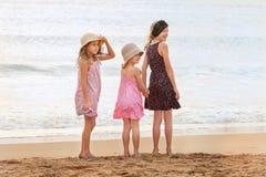 3 hermanas se colocan en mirar frente al mar detrás una persona en el sh Fotos de archivo