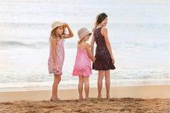 3 hermanas se colocan en mirar frente al mar detrás una persona en el sh Imagen de archivo