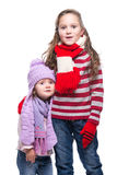 Hermanas sonrientes lindas que llevan el suéter, la bufanda, el sombrero colorido y los guantes hechos punto aislados en el fondo Imagenes de archivo