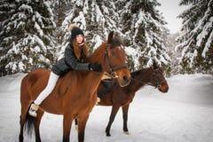 Hermanas y caballo gemelos en el bosque del invierno Fotos de archivo libres de regalías